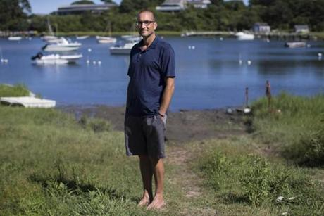 Chilmark, MA - 8/18/2016 - Filmmaker Thomas Bena, who's made a movie about the proliferation of large mansions on the of Martha's Vineyard, poses for a portrait in a pond across from one of the mansions in Chilmark, MA on the island of Martha's Vineyard, August 18, 2016. (Keith Bedford/Globe Staff)